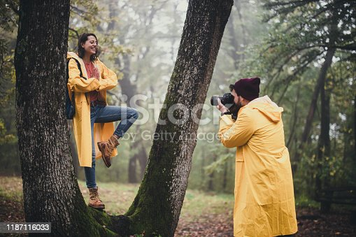 Happy woman in raincoat standing in tree pose while being photographer by her boyfriend in nature.