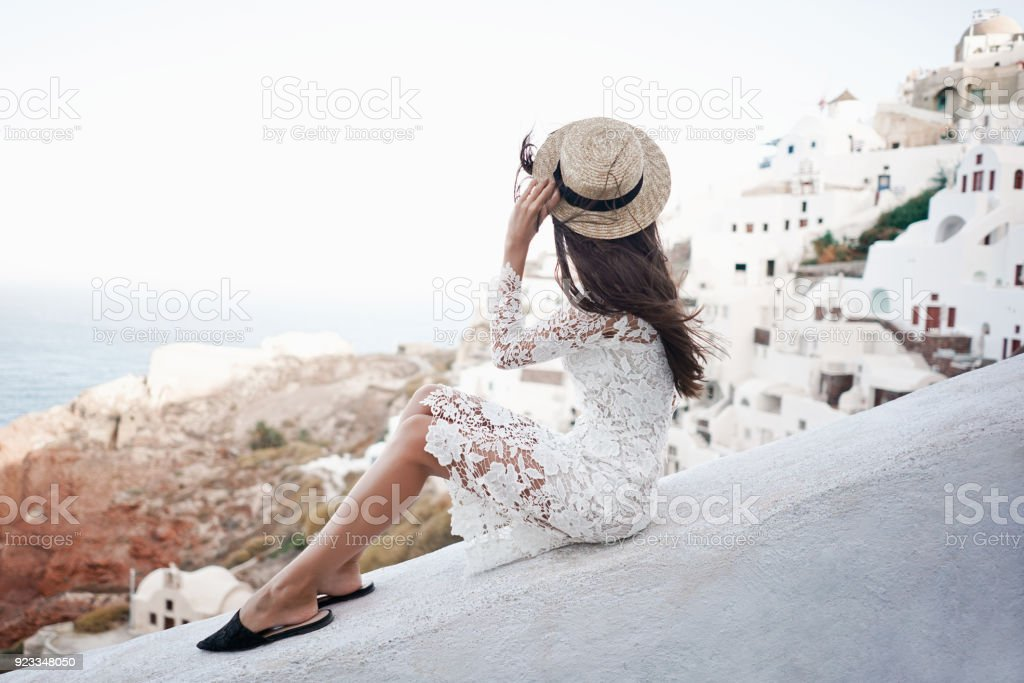 Happy woman in white dress and straw hat enjoying her holidays on Santorini stock photo