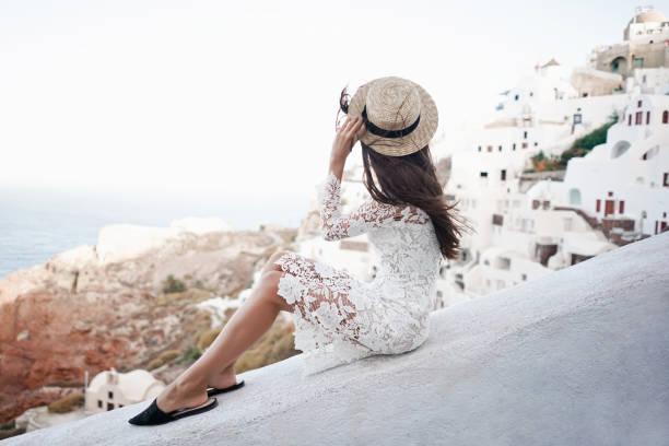 glückliche frau in weißem kleid und strohhut, genießen sie ihren urlaub auf santorini - soup_studio stock-fotos und bilder