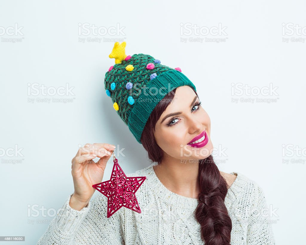 Happy woman in winter outfit holding red small star stock photo
