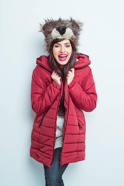 happy woman in winter outfit, wearing bear head fur hat - wintermantel damen wolle stock-fotos und bilder