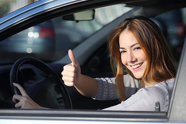glückliche frau in einem auto gestikulieren daumen nach oben - autos für fahranfänger stock-fotos und bilder