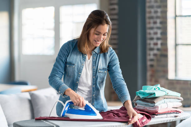 happy woman ironing her clothes at home - ironing stock photos and pictures