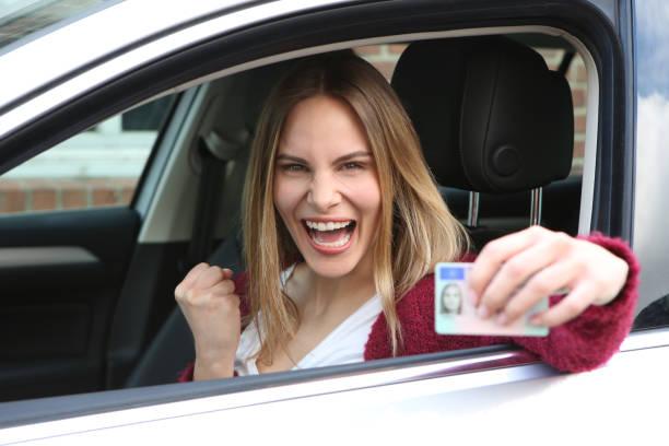 glückliche frau freut sich über die bestandene fahrprüfung und zeigt ihren führerschein - führerschein stock-fotos und bilder
