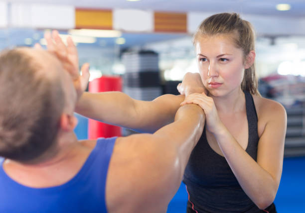 Happy woman is fighting with trainer Happy woman is fighting with trainer on the self-defense course for woman in sport club self defense stock pictures, royalty-free photos & images