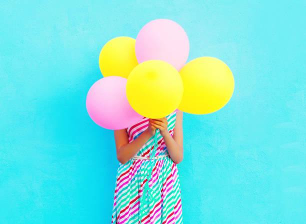 froh, dass frau ist ihr kopf verbirgt sich eine bunte luftballons spaß über einen blauen hintergrund - russisch hallo stock-fotos und bilder