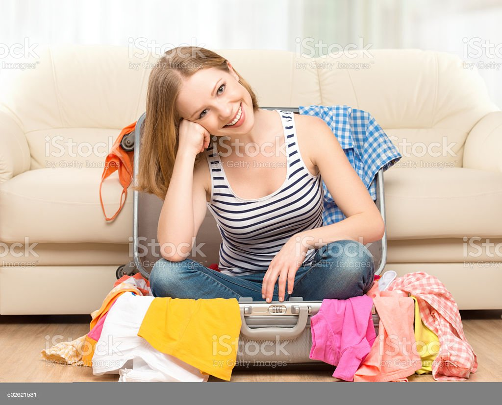 happy woman is packing suitcase at home stock photo
