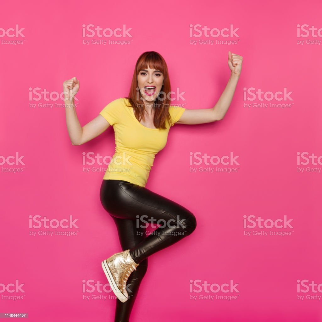 Happy young woman in yellow shirt is standing on one leg, holding...