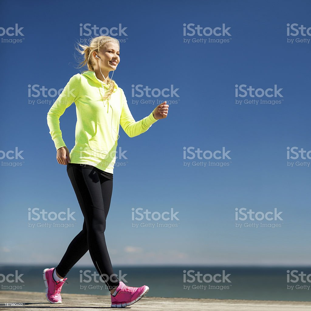 happy woman jogging outdoors stock photo