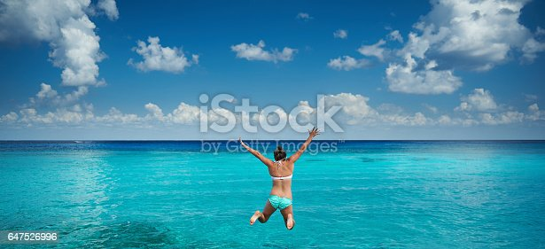 Happy woman jump to caribbean sea in blue sky background. Holiday in tropical resort