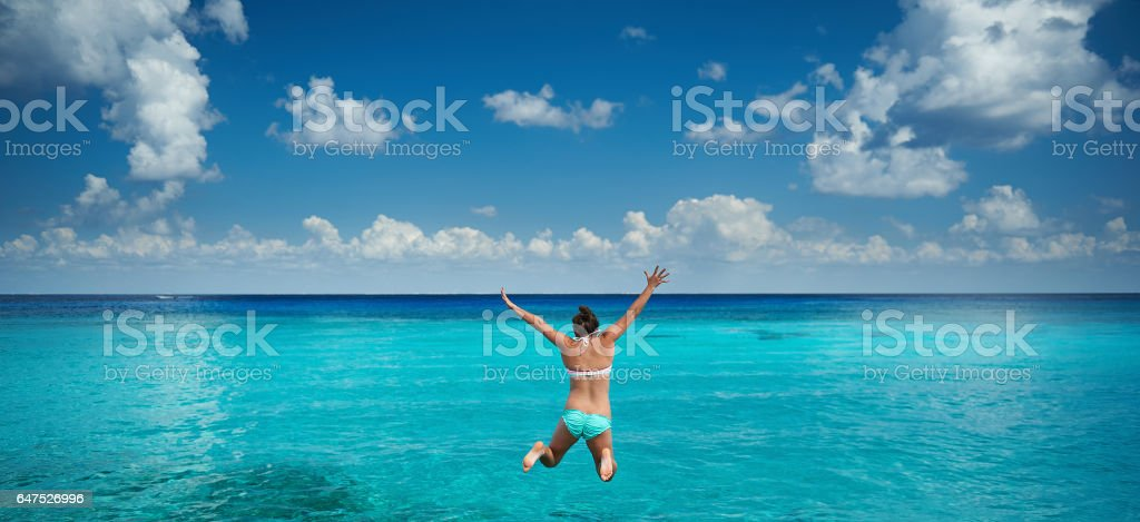 Happy woman jump to caribbean sea stock photo