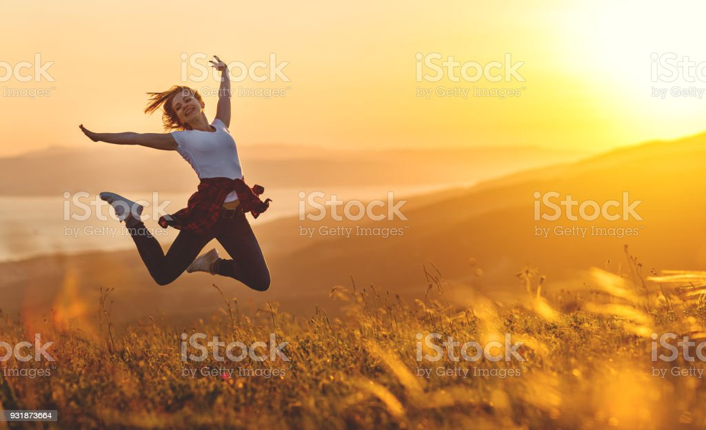 Happy woman jumping and enjoying life  at sunset in mountains stock photo