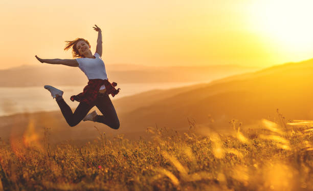 happy woman jumping and enjoying life  at sunset in mountains - vitality stock photos and pictures