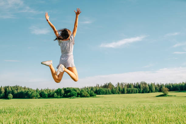 Happy woman jumping in green field against blue sky. Summer vacation concept stock photo