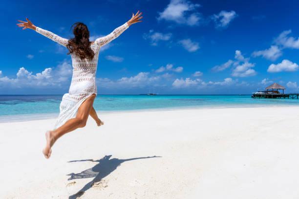Glückliche Frau springt der Aufregung an einem tropischen Strand – Foto