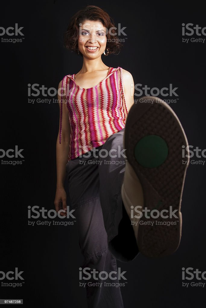 Happy woman kicking and showing her sport shoe royalty-free stock photo