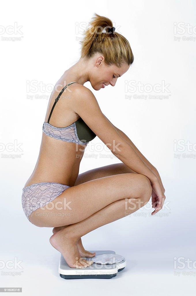 happy woman kneeling on bathroom scale royalty-free stock photo