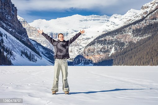 Woman expressing happiness at Lake Louise in Banff National Park Alberta Canada on a sunny winter day.
