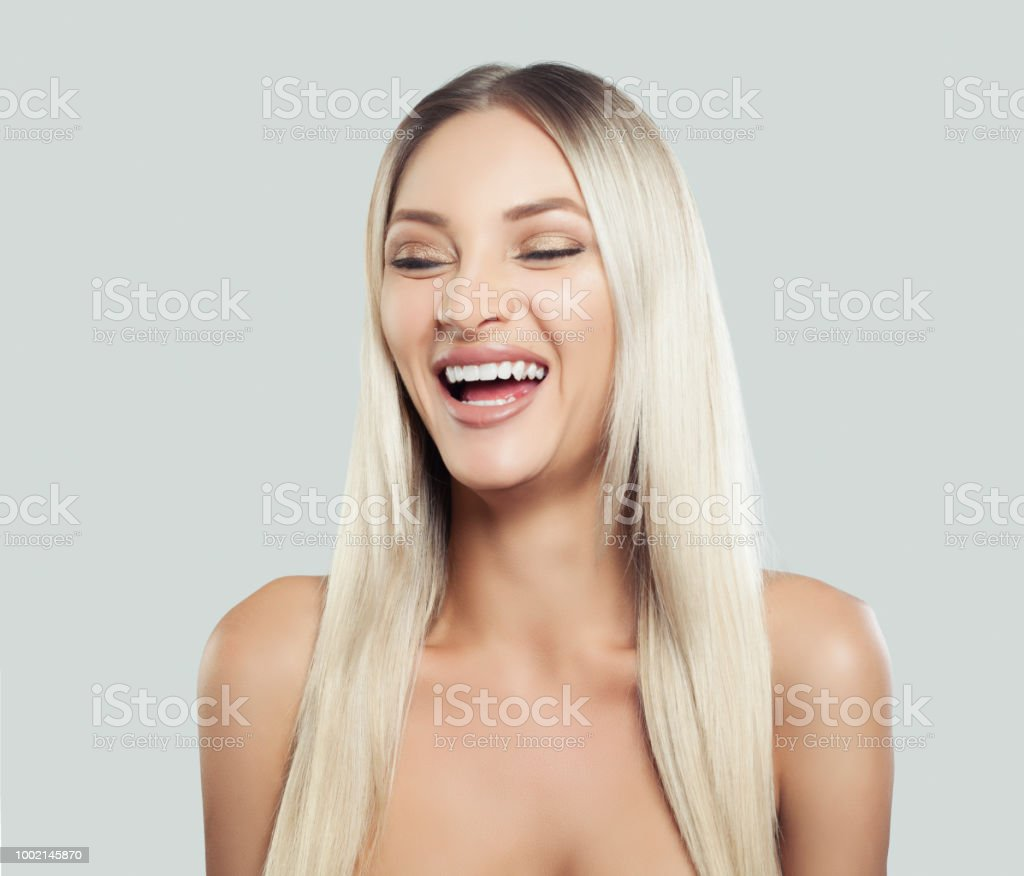 Happy Woman Laughing. Female Model with Long Healthy Blonde Hair on...