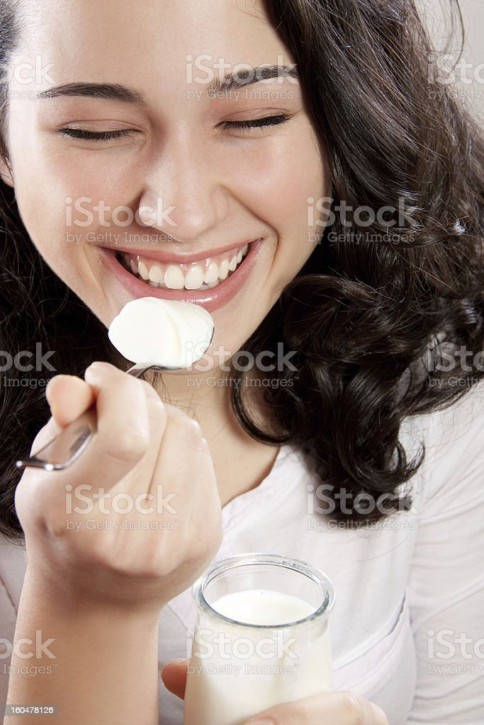 Happy woman laughing with eyes closed while eating a yogurt royalty-free stock photo