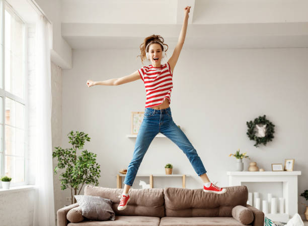 Happy woman listening to music and jumping and dancing on couch at home Excited young female in wireless headphones and casual clothes enjoying life while listening to music and jumping and dancing alone of sofa in cozy light apartment wireless headphones stock pictures, royalty-free photos & images