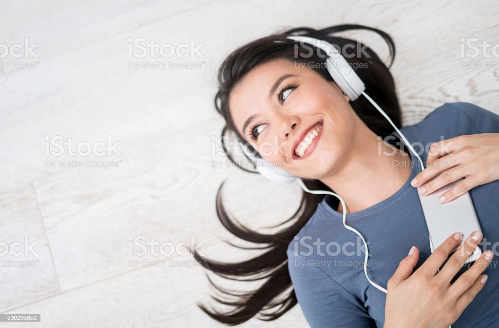 Happy woman listening to music at home royaltyfri bildbanksbilder