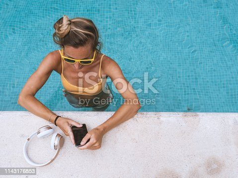 Happy woman listening to music with headphones bathing in swimming pool. blond girl enjoying free time by the pool with mobile phone.