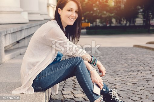 Smiling girl sitting on ground and looking at camera - copyspace