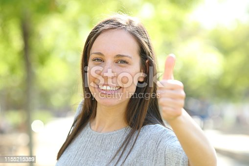 693589426istockphoto Happy woman looking at camera with thumbs up in a park 1155215389