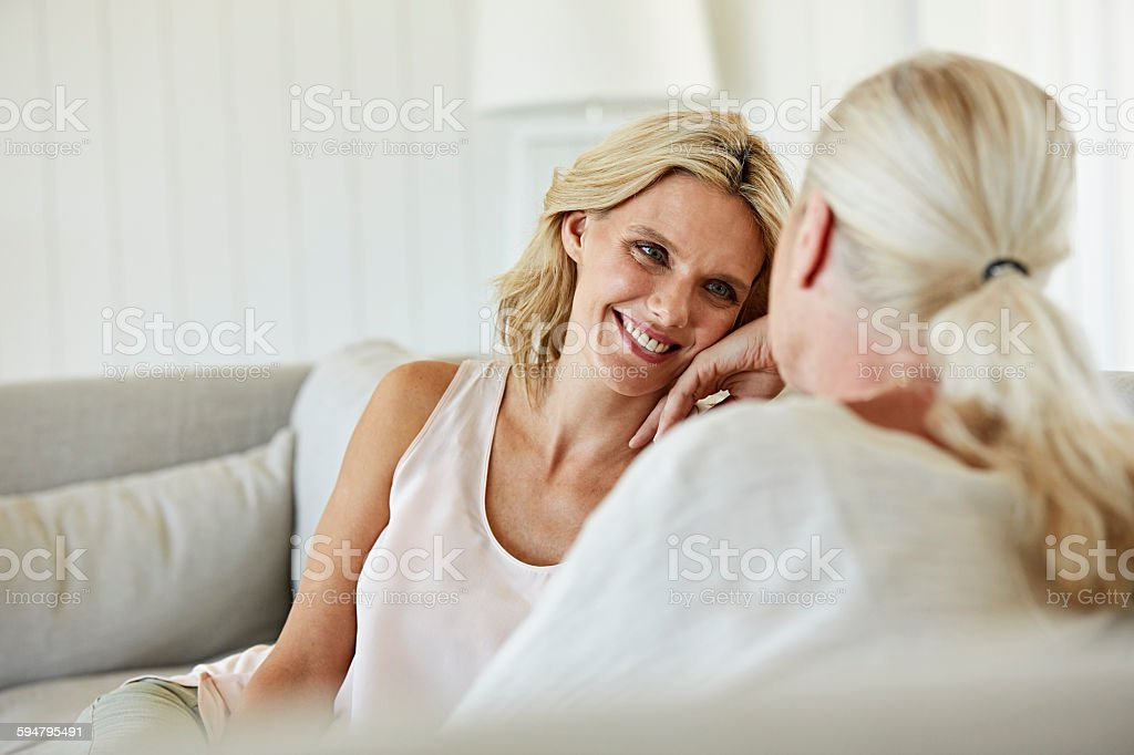 Happy woman looking at mother at home stock photo
