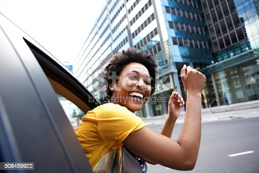 508455188 istock photo Happy woman looking out car window with her arms raised 508459922