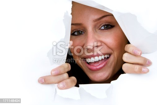 istock Happy woman looking through torn paper hole 171148404