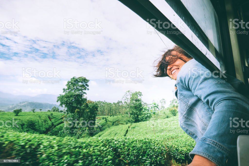 Happy woman looks out from train window during traveling on most picturesque train road in Sri Lanka stock photo