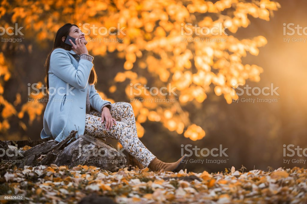 Happy woman making a phone call during an autumn day in nature. stock photo