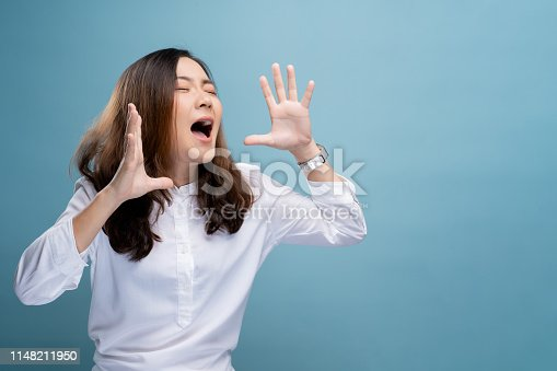 820421282istockphoto Happy woman making shout gesture isolated over blue background 1148211950