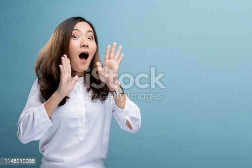 820421282istockphoto Happy woman making shout gesture isolated over blue background 1148212035