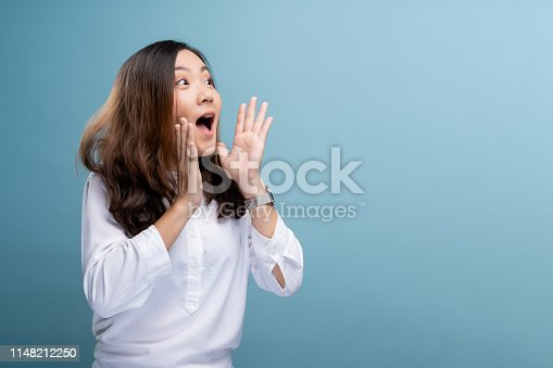 820421282istockphoto Happy woman making shout gesture isolated over blue background 1148212250