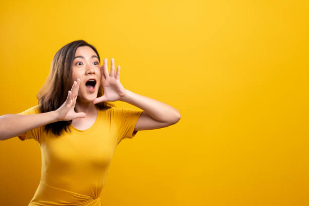 Happy woman making shout gesture isolated over yellow background stock photo
