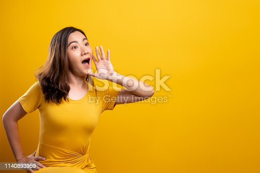 820421282istockphoto Happy woman making shout gesture isolated over yellow background 1140893959