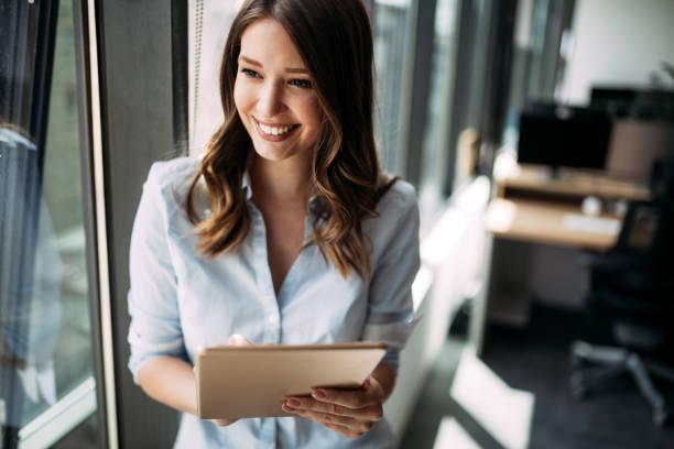 glückliche frau manager tablet halten und stehen im modernen büro - weibliche führungskraft stock-fotos und bilder