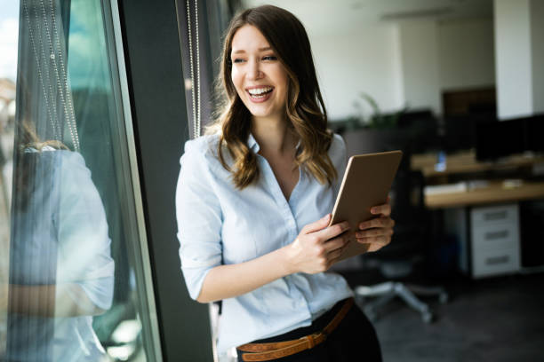 Happy woman manager holding tablet and standing in modern office stock photo