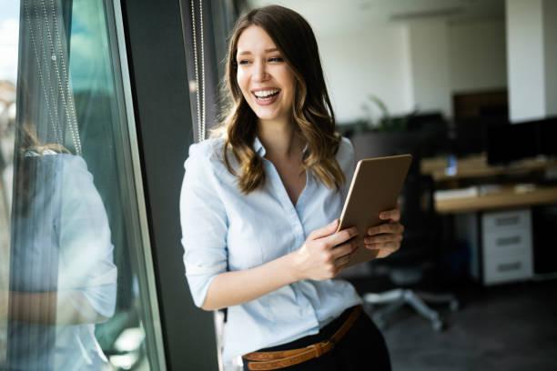 Glückliche Frau Manager hält Tablet und steht in modernen Büro – Foto
