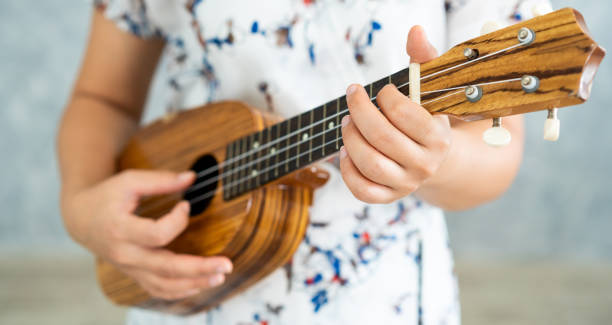 Happy woman musician playing ukulele and singing a song in sound studio. Music lifestyle concept. stock photo
