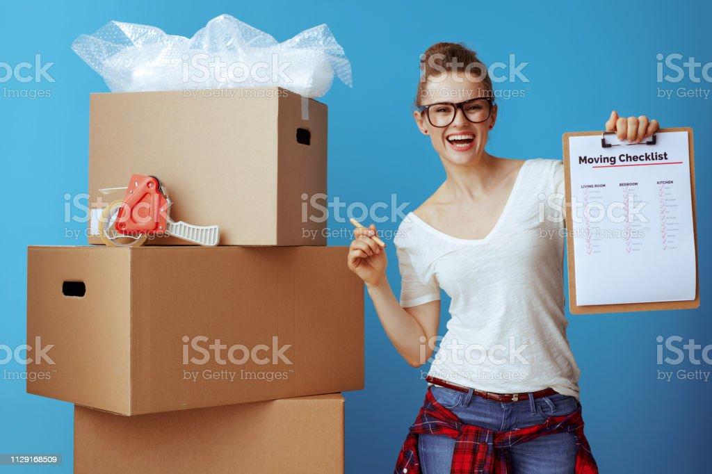 glückliche Frau in der Nähe von Karton mit beweglichen Checkliste auf blau – Foto