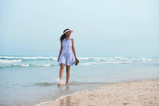 幸せな女夏の浜辺を歩きます。 - 水につかる ストックフォトと画像