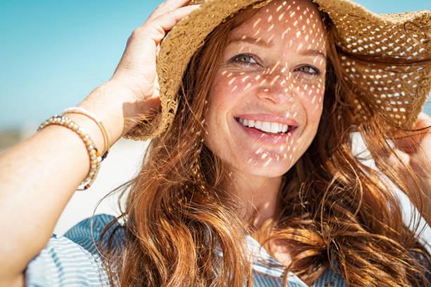 Glückliche Frau am Strand trägt Strohhut – Foto