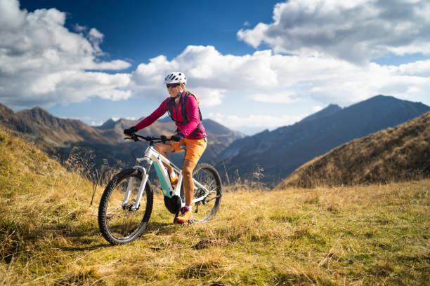glückliche frau auf elektro mountain bike hoch oben im europäischen berge - elektrorad stock-fotos und bilder