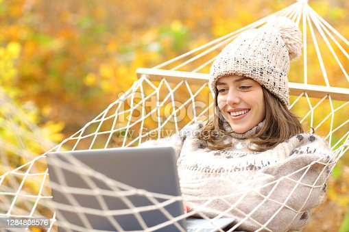 istock Happy woman on hammock using laptop in autumn 1284808576