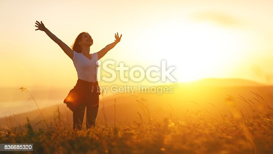 istock Happy woman   on sunset in nature iwith open hands 836685320