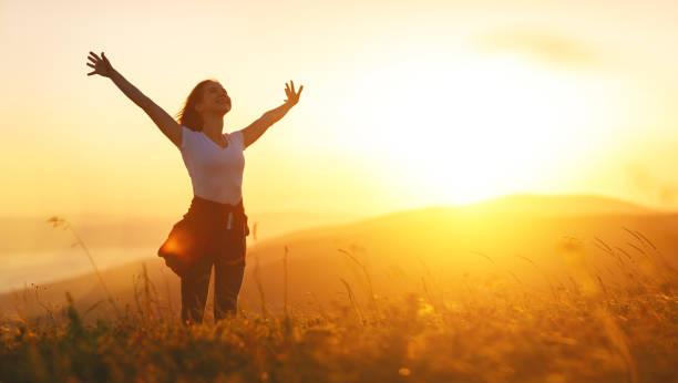 glückliche frau auf sonnenuntergang in natur imit offene hände - gegenlicht stock-fotos und bilder